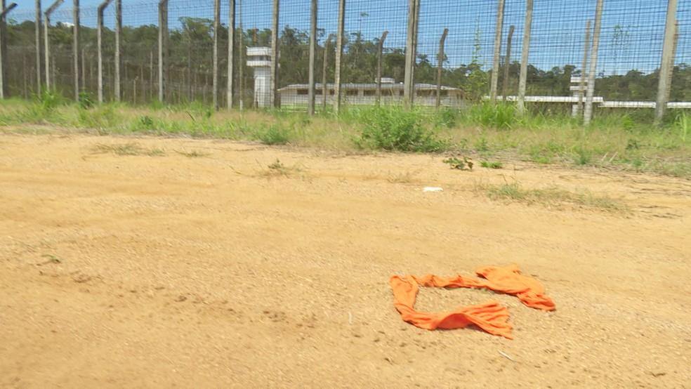 Uniformes dos presos se rasgaram durante a fuga e ficaram próximo a cerca de proteção do presídio (Foto: Rede Amazônica/Reprodução)
