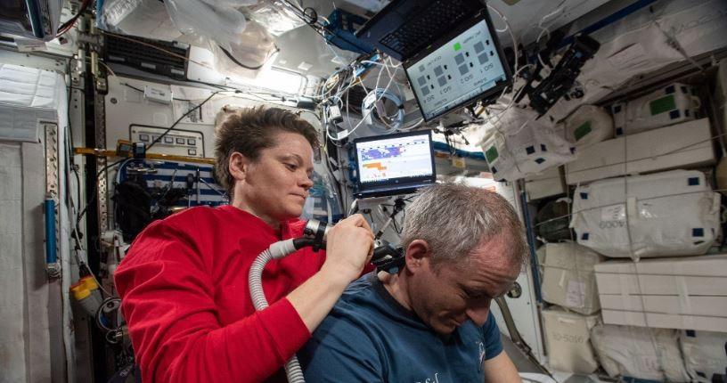 Astronautas utilizam aparelho de sucção para sugar fios após corte de cabelo  (Foto: NASA)