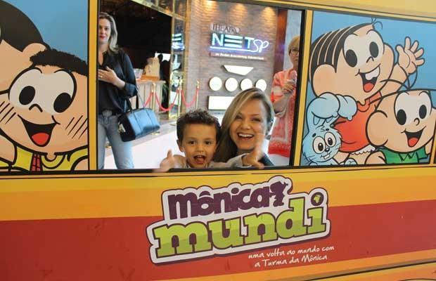 Eliana e Arthur se divertem com painel, em formato de ônibus, na entrada do teatro (Foto: Divulgação)