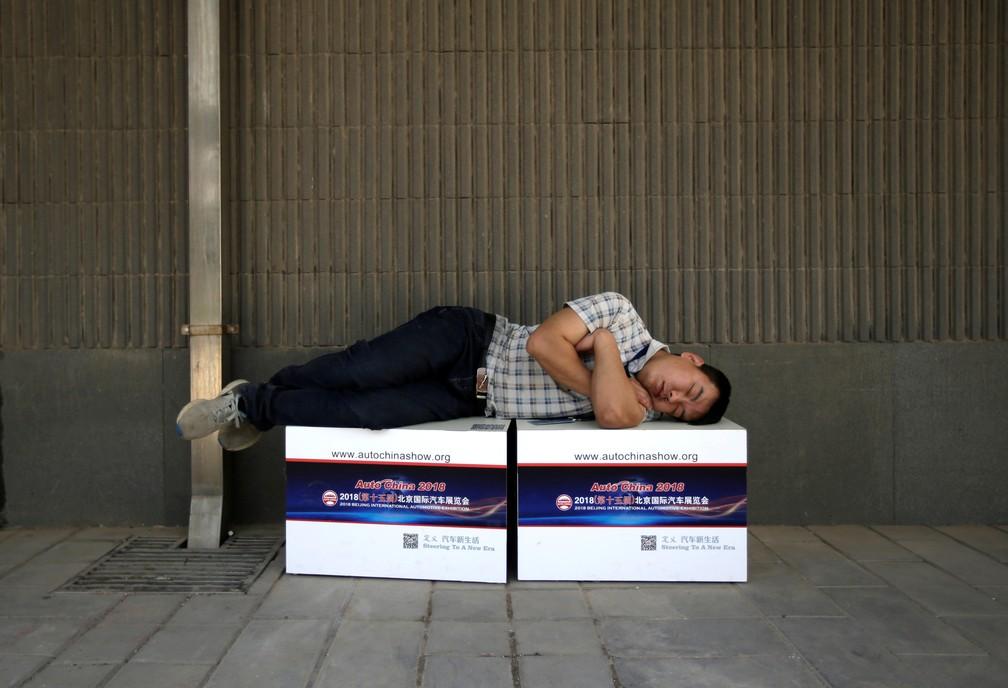 Homem dorme em caixas promocionais do Salão de Pequim 2018 (Foto: Jason Lee/Reuters)