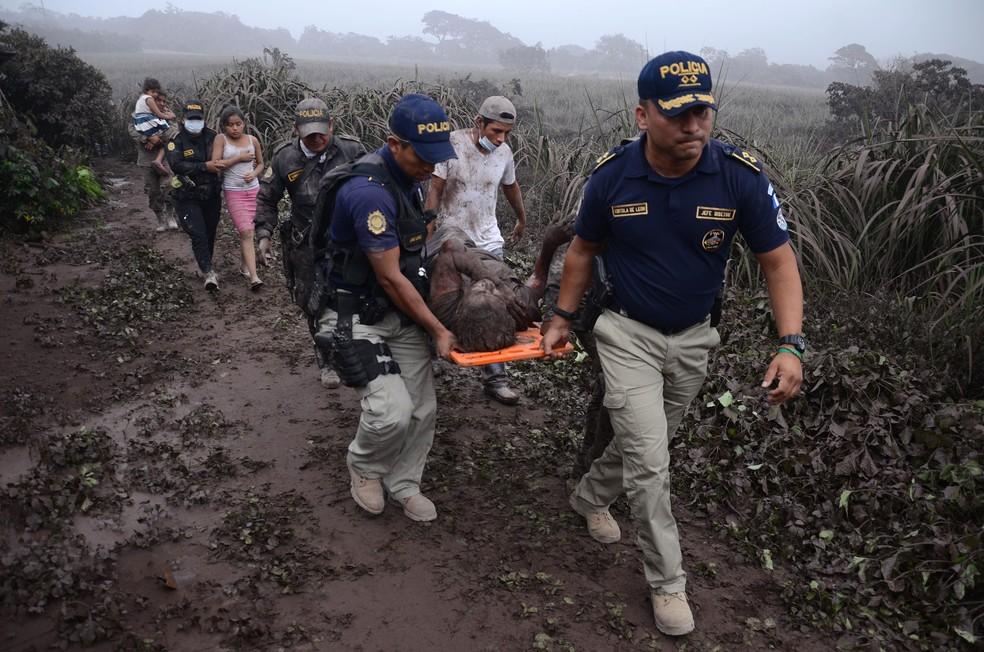 Policiais carregam ferido na erupção do Vulcão do Fogo, em El Rodeo, no departamento de Escuintla, no domingo (3)  (Foto: Noe Perez / AFP)