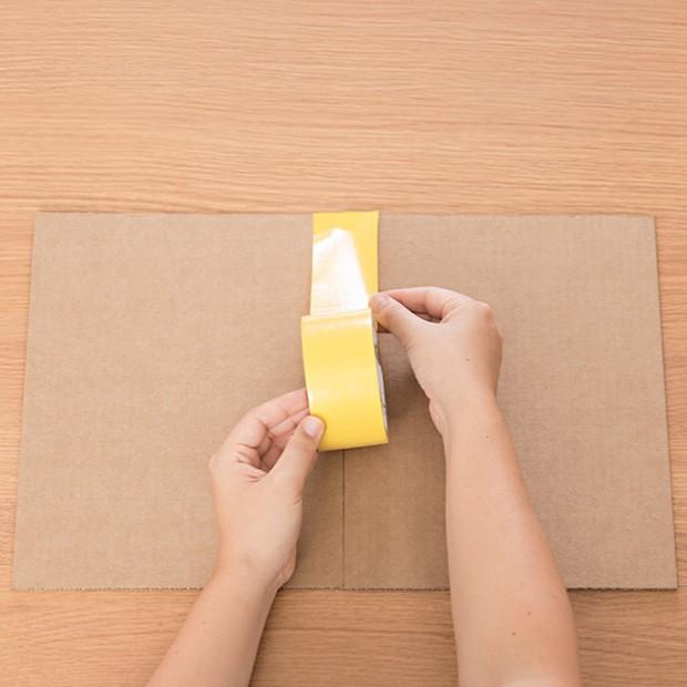 2. Cole as duas placas de papelão com fita adesiva no centro. Faça o mesmo do outro lado, para garantir que fiquem bem presas. (Foto: Bruno Marçal / Editora Globo)