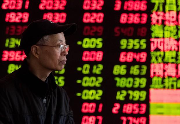 Investidor observa painel na Bolsa de Valores de Xangai ; ações chinesas ; mercado financeiro asiático ;  (Foto: ChinaFotoPress/Getty Images)