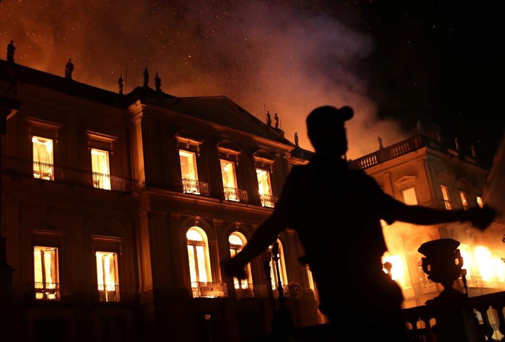 Um policial é visto durante incêndio no prédio do Museu Nacional, no Rio de Janeiro, na noite de domingo (2) (Foto: Ricardo Moraes/Reuters)