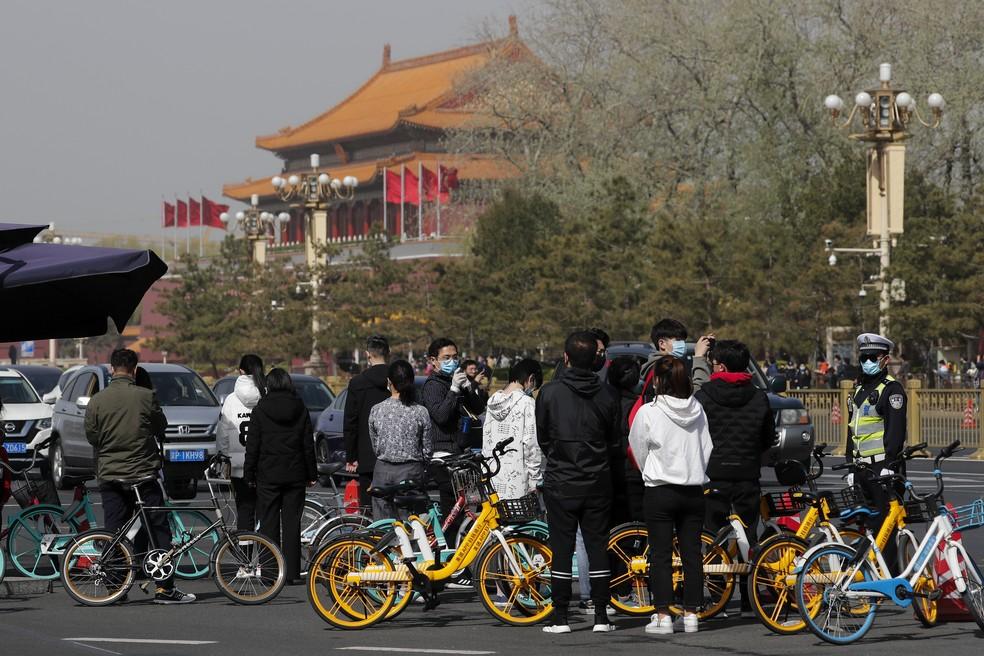 Um grupo de pessoas faz uma pausa perto da Praça da Paz Celestial, em Pequim, para em homenagem aos mortos pelo novo coronavírus — Foto: Andy Wong / AP Photo
