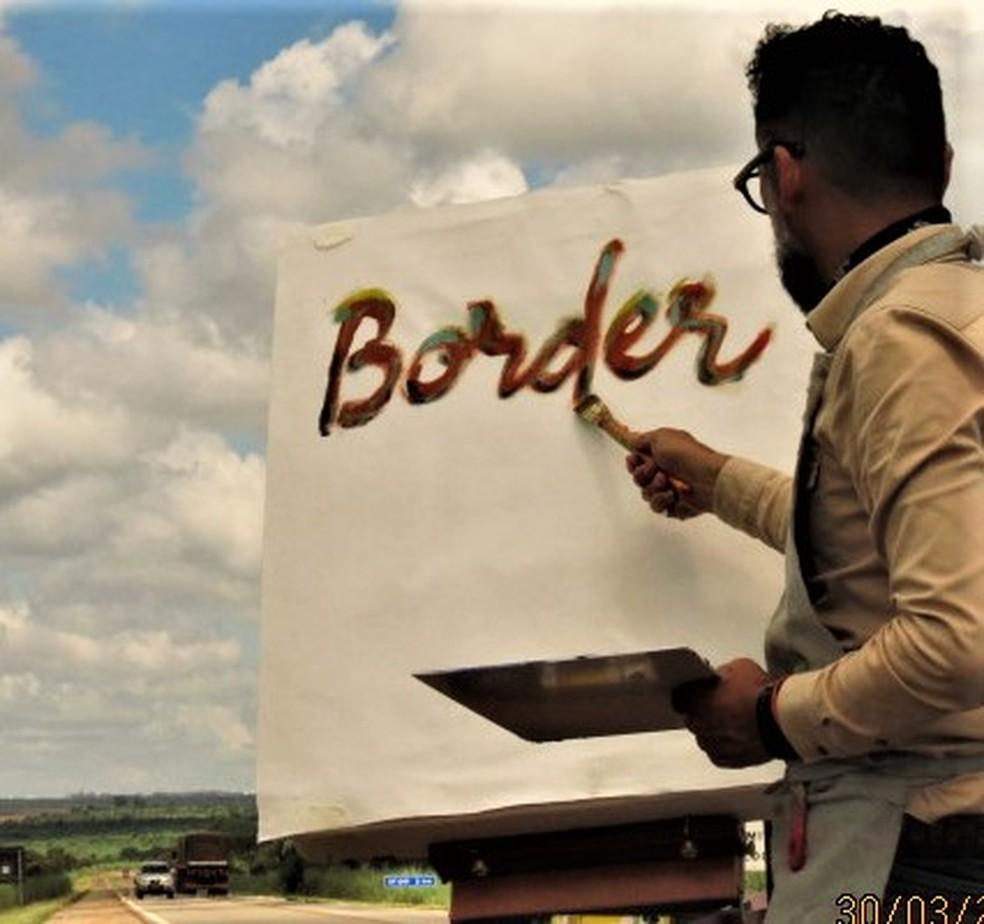 Militão pinta a palavra Border em quadro no meio da estrada, nome do projeto da viagem — Foto: Carlos Bueno/TV Globo