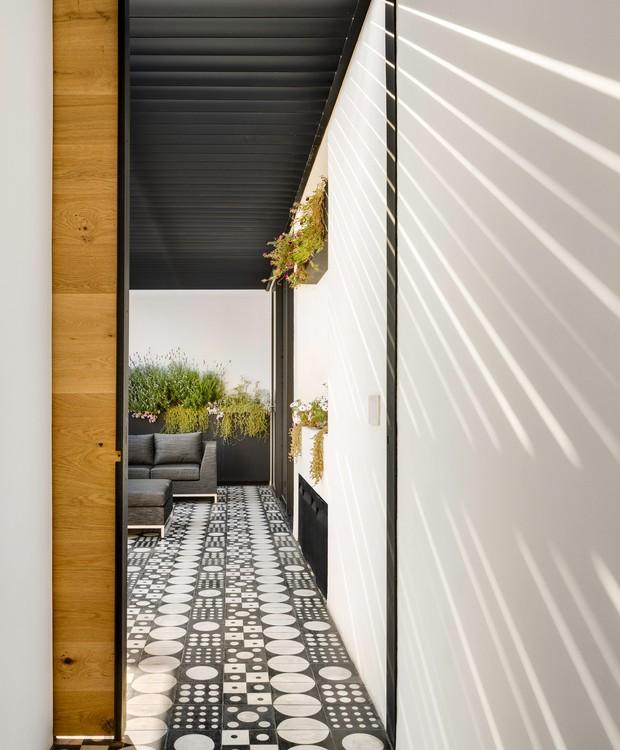 Um terraço amplo possui porta de correr de madeira na entrada. Nessa parte do jardim, uma goiabeira recebe bastante luz solar (Foto:  Rafael Gamo/ Reprodução)