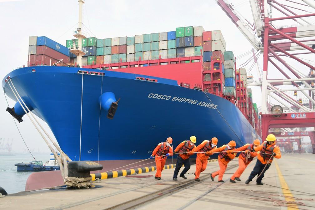 Trabalhadores vestem máscaras enquanto trabalham no porto em Qingdao, na China — Foto: China Daily via REUTERS
