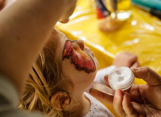 Pessoa pintando o rosto de criança (Foto:  )
