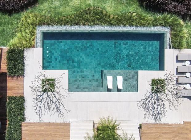 Vista aérea | De cima, é possível admirar o desenho criado com duas variações de capim-do- texas: o verde foi plantado rente à piscina e o rubro, nas margens do terreno. Entre eles, grama-esmeralda (Foto: Iuri Seródio/Divulgação)