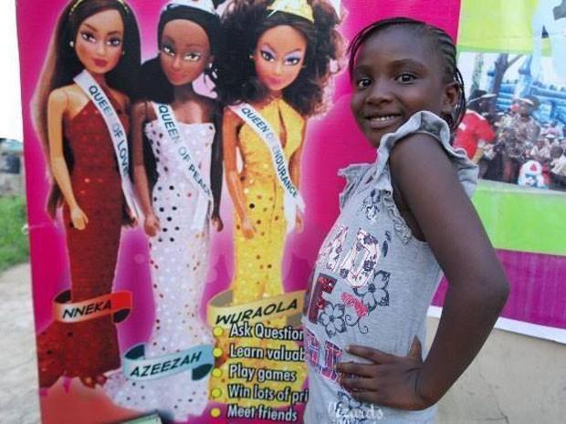 Criança em frente a caixas com as bonecas (Foto: Queens of Africa/Divulgação)