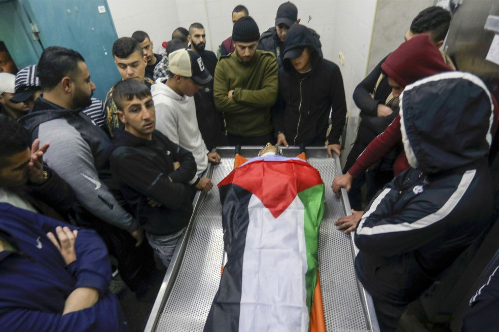 Familiares lamentam morte de jovem de 19 anos em Jenin, na Cisjordânia, nesta quinta-feira (6) — Foto:  Jaafar Ashtiyeh / AFP