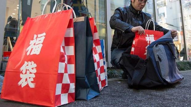 A palavra fukubukuro, em japonês, aparece escrito nessas bolsas vermelhas de papel (Foto: Getty Images via BBC News Brasil)