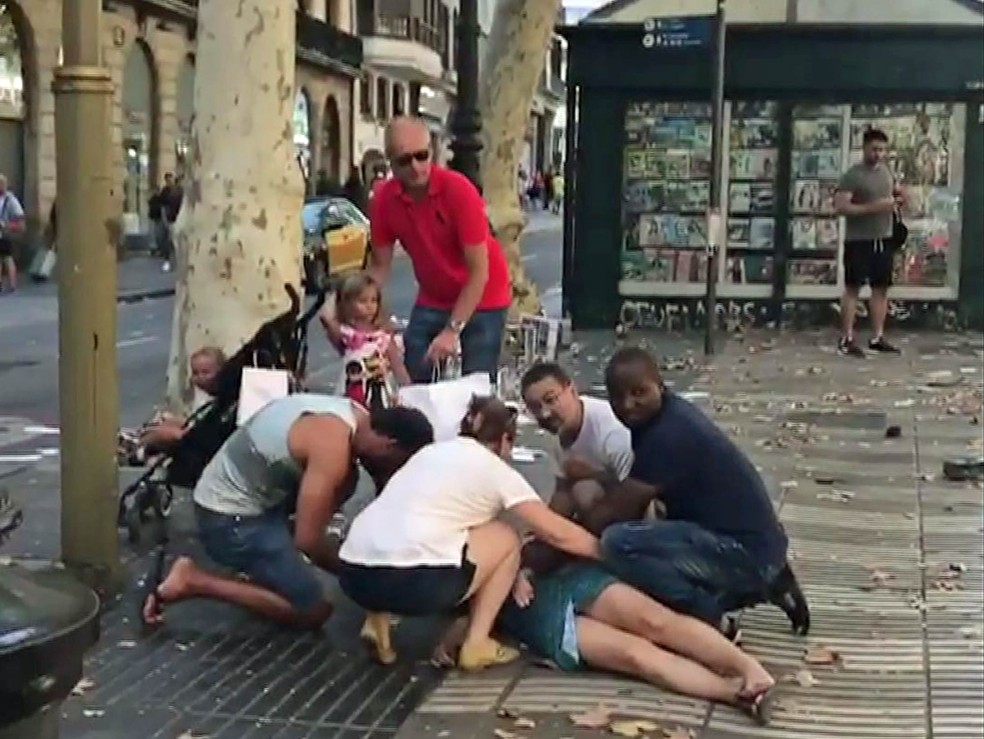 Grupo socorre um ferido no atentado que deixou mortos na área de Las Ramblas em Barcelona (Foto: Reprodução/carlos_tg_32_/Instagram via Reuters)