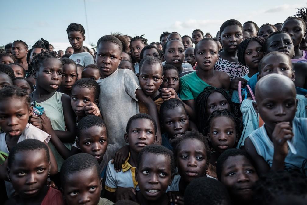 Crianças esperam para receber comida de um supermercado local em um centro de evacuação em Dondo, a cerca de 35km de Beira, nesta quarta (27). — Foto: Yasuyoshi Chiba/AFP