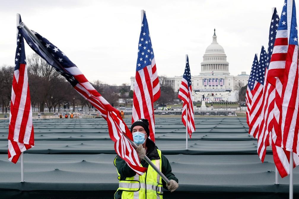 Funcionário prepara memorial das vítimas da Covid-19 com bandeiras dos EUA em frente ao Capitólio nesta terça (19), véspera da posse de Joe Biden — Foto: Carlos Barria/Reuters