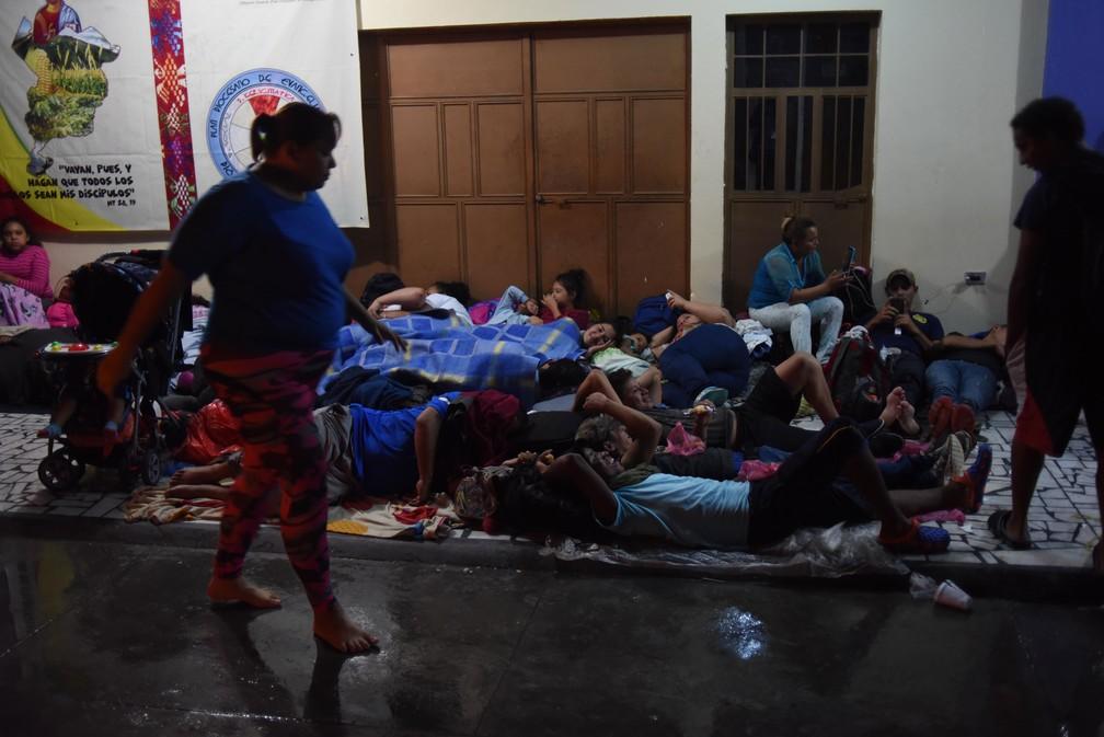 Imigrantes hondurenhos integrantes de caravana que segue para os Estados Unidos descansam no chão da igreja em Tecún Umán, na fronteira com o México, na noite de quinta-feira (18)  — Foto: Johan Ordonez / AFP