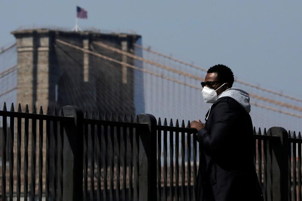 Homem usa máscara ao caminhar no Brooklyn, em Nova York, neste domingo (19) — Foto: Andrew Kelly/Reuters