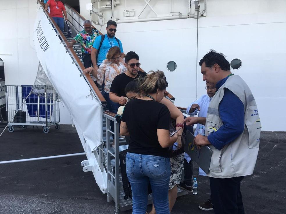 Passageiros deixam o navio MSC Seaview após tomarem vacina contra o sarampo, em Santos — Foto: Solange Freitas/G1
