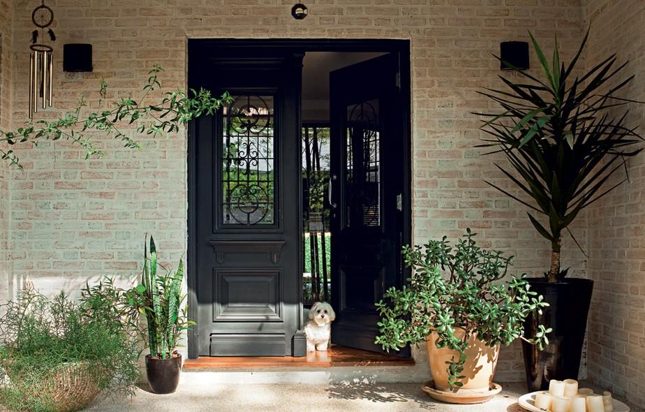 De estilo inglês, a porta antiga de duas folhas de madeira entalhada deu ar imponente à entrada da casa, construída pela designer Adriana Moraes, há 20 anos, para sua família. Comprada em uma loja de demolição, ela recebeu pintura automotiva preta