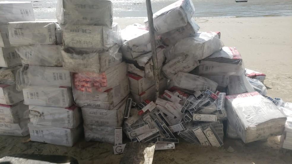 Parte da carga de cigarros ilegais retiradas do barco e reunidas na Praia do Mangue Seco, em Raposa — Foto: Divulgação/Polícia Civil