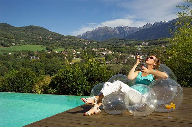 Mulher sentada em cadeira inflável que tem forma de nuvem, perto de um piscina  (Foto: Reprodução)