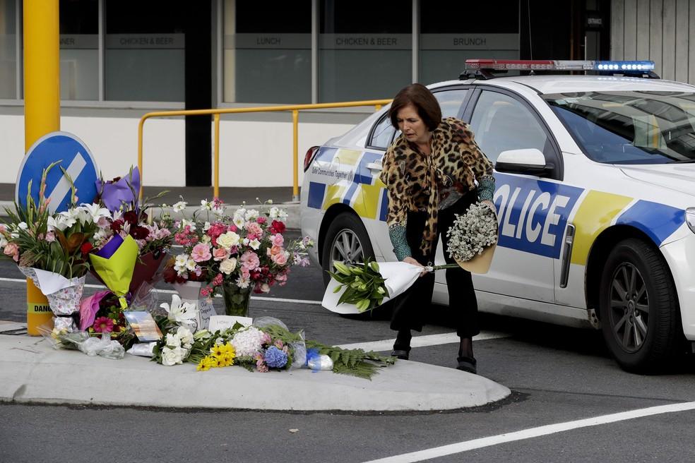 Mulher deposita buquê de flores em homenagem a mortos em atentado a mesquita em Christchurch, Nova Zelândia — Foto: Mark Baker/AP Photo