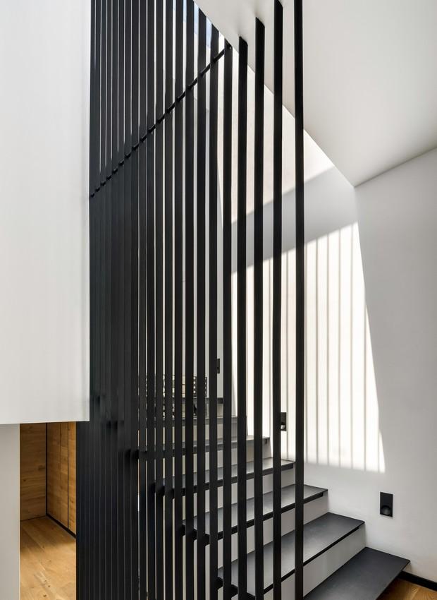 No inteiror, a escada que leva ao ultimo andar possui uma divisória vazada, feita de ripas pretas de aço (Foto:  Rafael Gamo/ Reprodução)