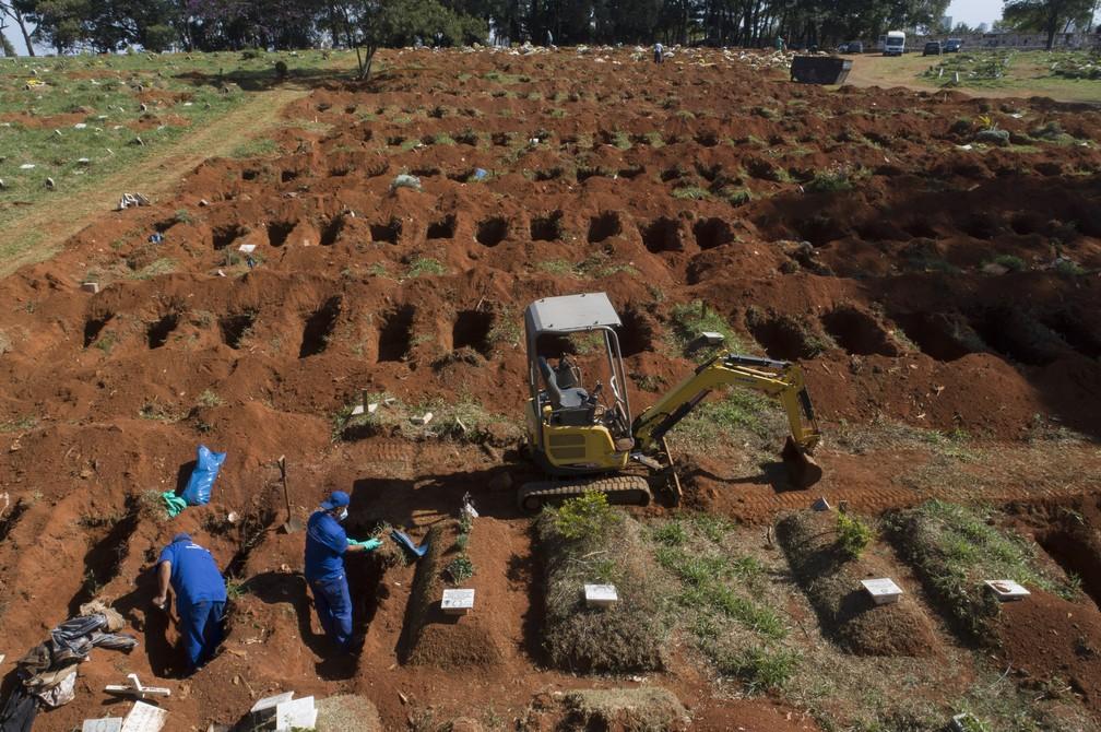 12 de junho de 2020 - Coveiros fazem exumação de corpos enterrados há 3 anos no cemitério da Vila Formosa, em São Paulo, durante a pandemia do novo coronavírus no Brasil — Foto: Andre Penner/AP