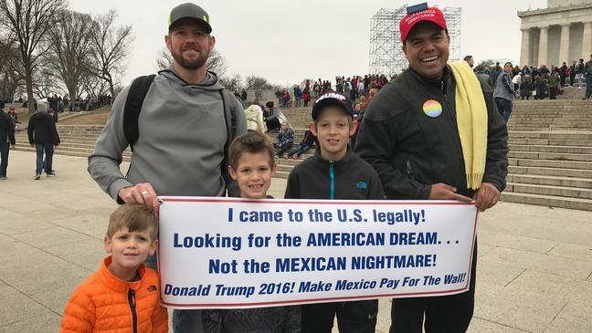 """Shane Stevens, os filhos e um apoiador não identificado de Trump no dia em que o presidente tomou posse em 2017. Na placa, lê-se: """"Vim para os Estados Unidos legalmente. Procurando o sonho americano e não o pesadelo mexicano. Donald Trump 2016. Faça o México pagar pelo muro"""" (Foto: Reprodução Facebook)"""