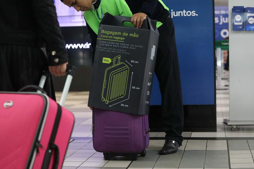 Um fiscal confere as medidas da bagagem de passageiros na entrada da sala de embarque do aeroporto de Congonhas, em São Paulo. — Foto: Renato S. Cerqueira / Futura Press / Estadão Conteúdo