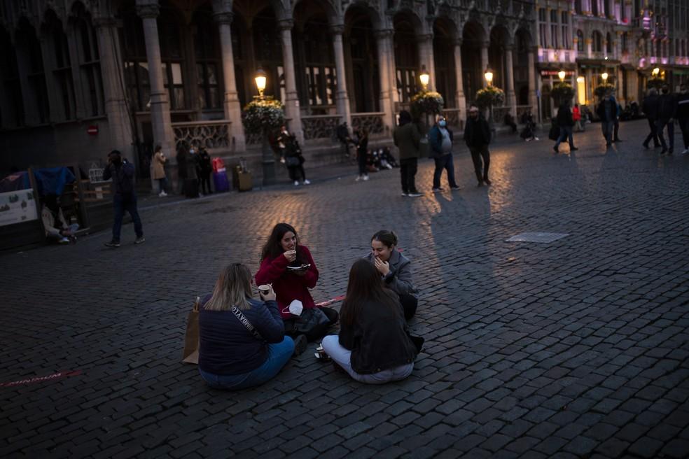 Estudantes espanhóis comem waffles na Grand Place na sexta-feira (23), no centro de Bruxelas, antes do toque de recolher — Foto: Francisco Seco/AP