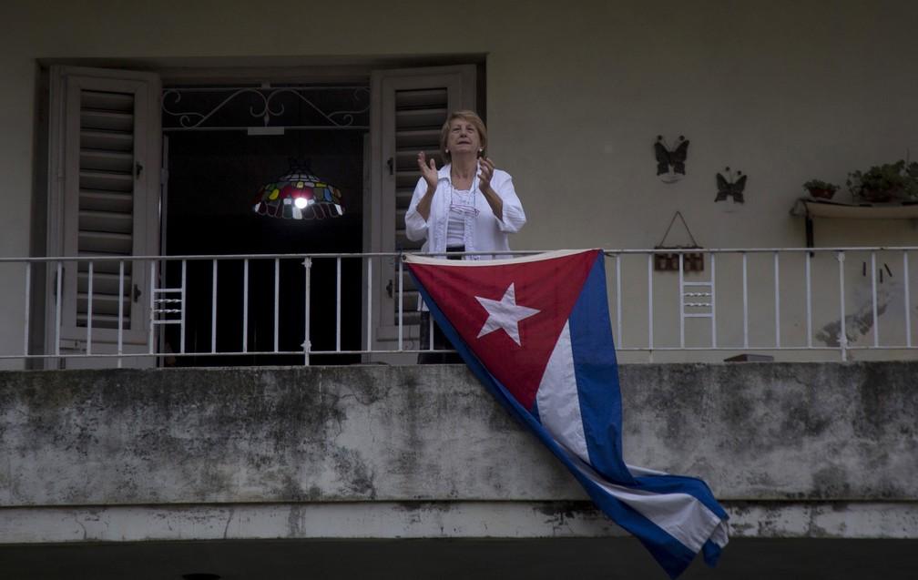 Mulher aplaude da varanda de sua casa em comemoração ao Dia do Trabalho, em Havana, Cuba — Foto: Ismael Francisco/AP