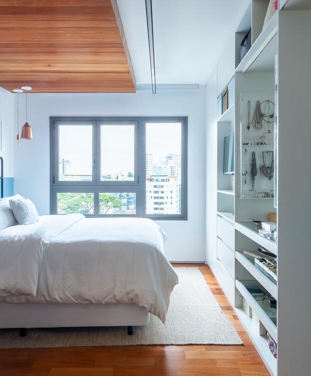 Um forro da mesma madeira do piso ocupa a área sobre a cama e multiplica a sensação de acolhimento (Foto: Pedro Napolitano Prata/Divulgação)