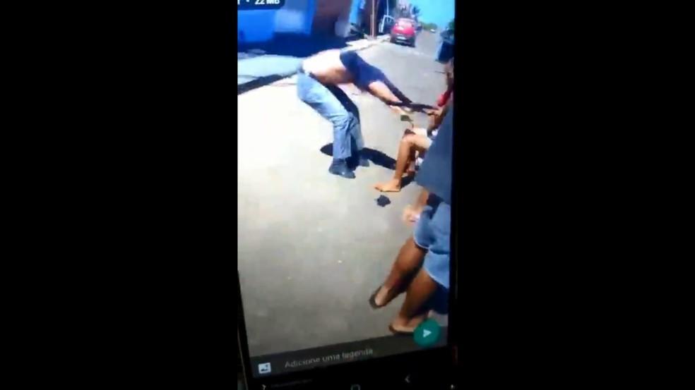 Policial é segurado pela camiseta por moradora após ser agredido — Foto: Reprodução