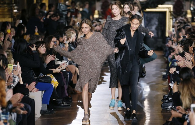 British model Cara Delevingne (L) and Puerto Rican model Joan Small (R) dance as they present creations by Stella McCartney during the 2014/2015 Autumn/Winter ready-to-wear collection fashion show, on March 3, 2014 in Paris.  AFP PHOTO / PATRICK KOVARIK   (Foto: AFP/Getty Images)