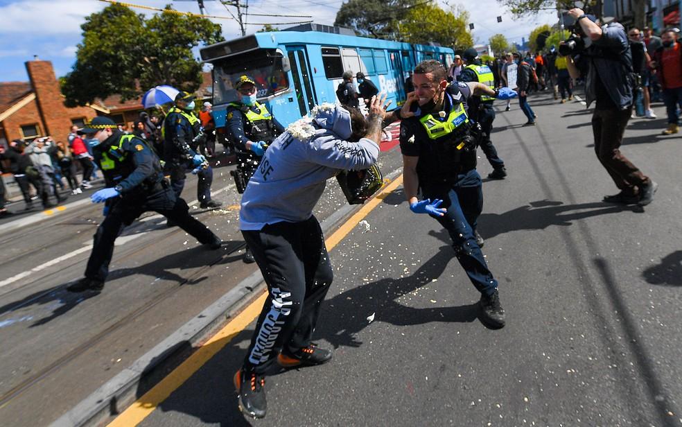 Policiais disparam spray de pimenta durante confronto com manifestantes contra o confinamento em Melbourne, na Austrália, no sábado (18) — Foto: James Ross/AAP Image via AP