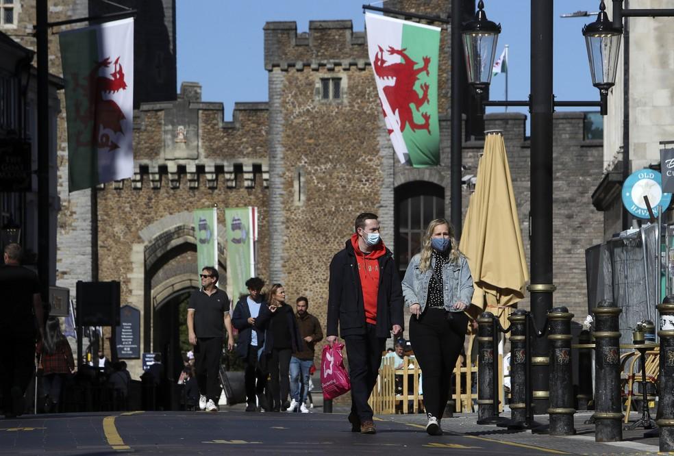 Casal anda de máscaras para proteção contra a Covid-19 em Cardiff, sul do País de Gales, no dia 27 de setembro. — Foto: Geoff Caddick / AFP