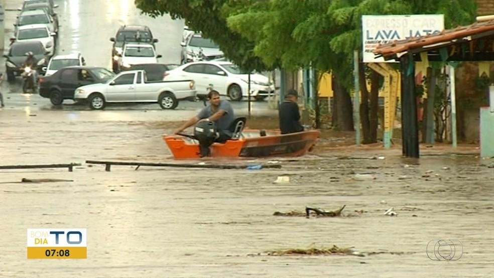 Moradores usam barco para navegar por ruas (Foto: Reprodução/TV Anhanguera)