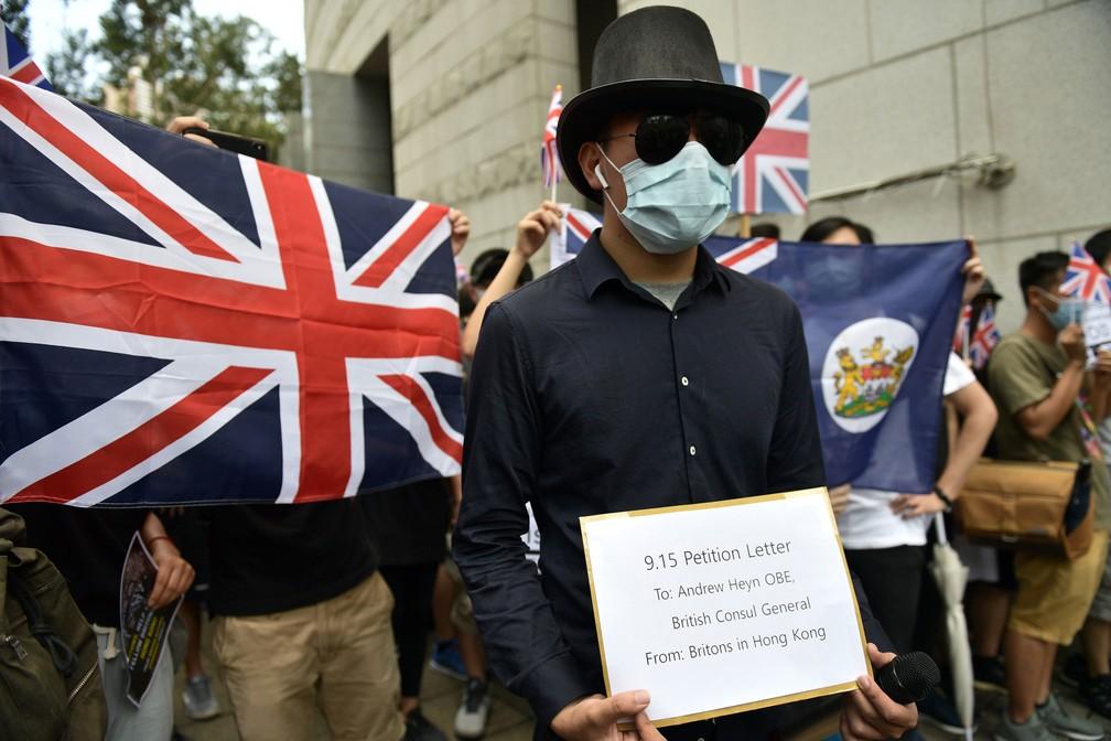 Ativista pró-democracia faz protesto em frente ao consulado britânico em Hong Kong neste domingo (15)  — Foto: Nicolas Asfouri / AFP