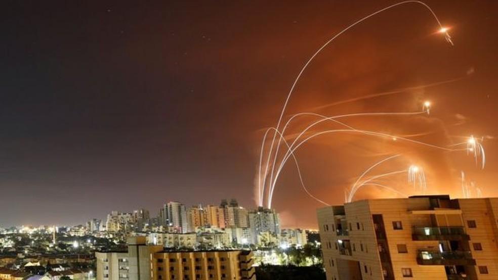 Faixas de luz são vistas em Ashkelon no momento em que o sistema antimísseis Domo de Ferro de Israel intercepta foguetes lançados de Gaza — Foto: Reuters/Via BBC