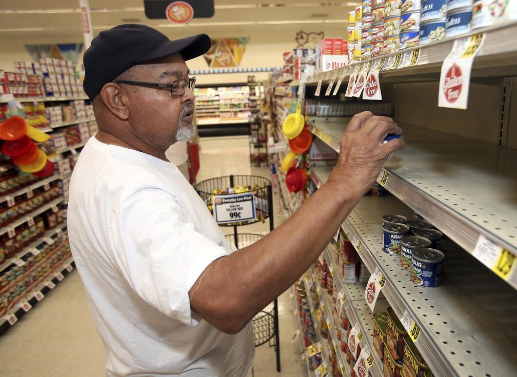 Morador de Rocky Mount, na Carolina do Norte, compra produto enlatado antes da chegada do furacão Florence — Foto: Alan Campbell/Rocky Mount Telegram via AP