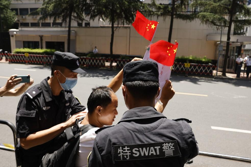 Manifestante chinês é retirado por policiais depois de gritar palavras pró-China do lado de fora do consulado dos Estados Unidos em Chengdu, na província de Sichuan, na China, nesta segunda (27) — Foto: Ng Han Guan/AP