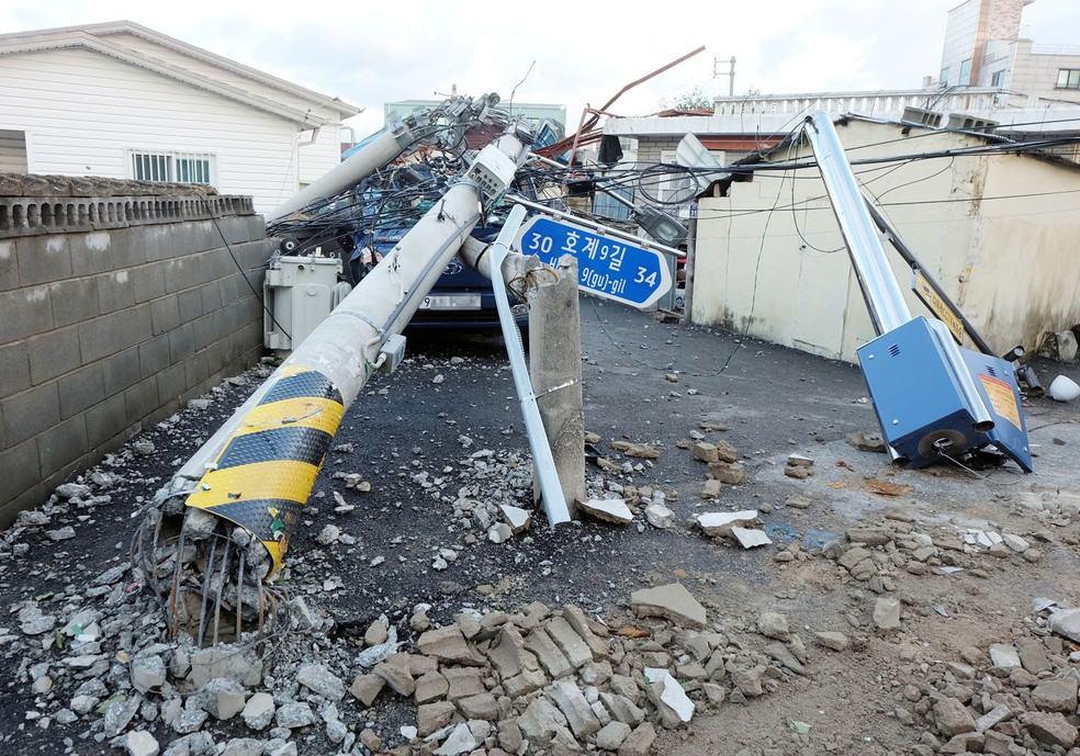 Um poste de eletricidade é visto caído uma rua danificada pelo tufão Maysak em Ulsan, na Coreia do Sul, nesta quinta-feira (3) — Foto: Yonhap via Reuters