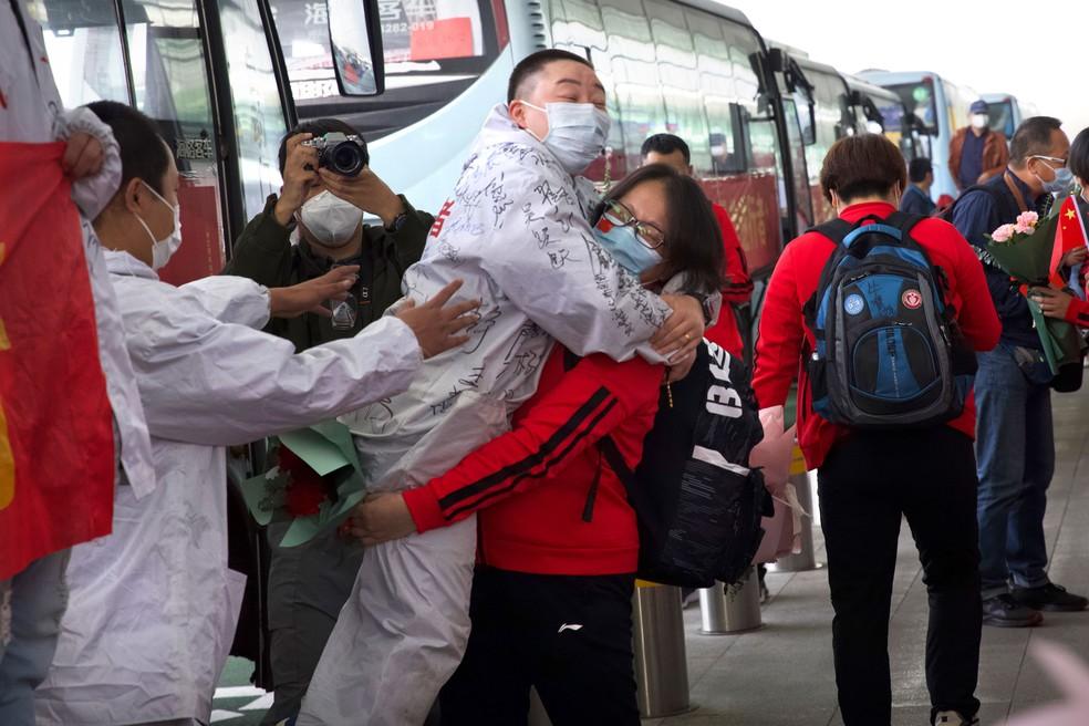 Médica da província de Jilin, na China, abraça colega de Wuhan enquanto se prepara para voltar para casa no Aeroporto Internacional Wuhan Tianhe, em Wuhan, nesta quarta-feira (8) — Foto: Ng Han Guan/AP