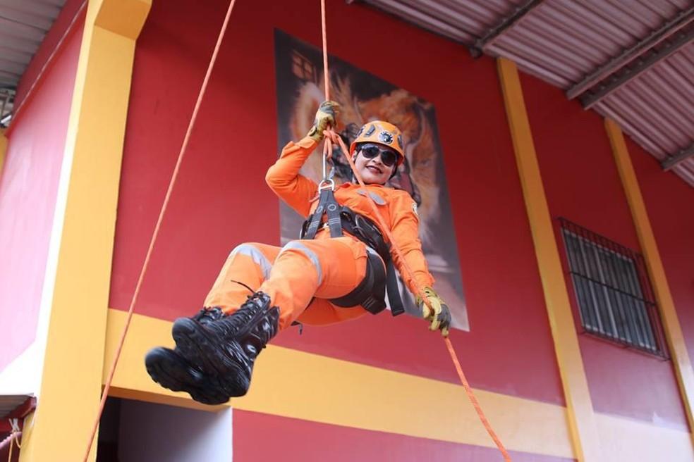 Mulher bombeira em treino de operação de resgate, na exposição 'Trabalho de Mulher' — Foto: Luciana Macedo/Divulgação