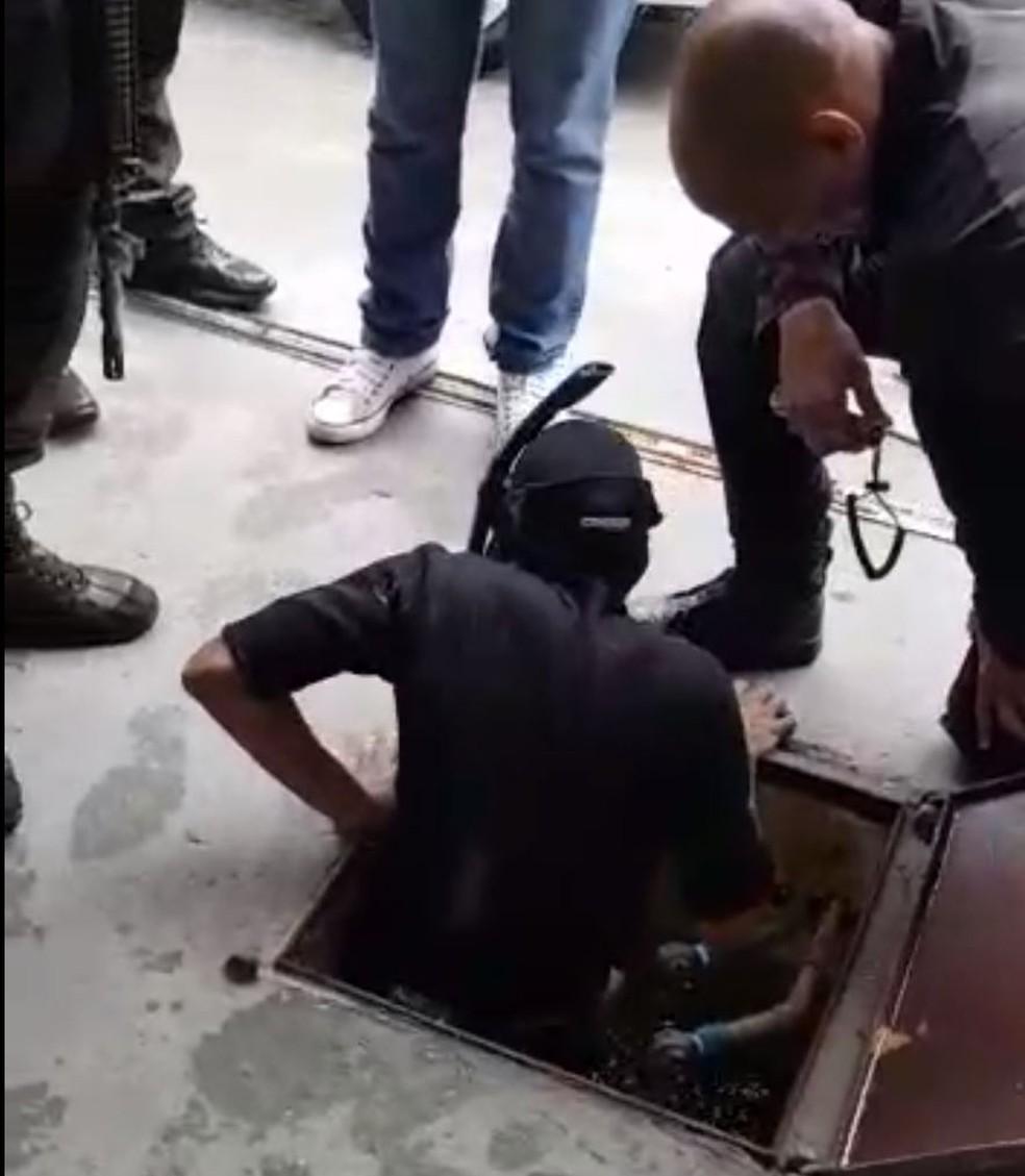 Mergulhador entra em bueiro de condomínio para tentar encontrar armas usadas na morte de Marielle — Foto: Reprodução