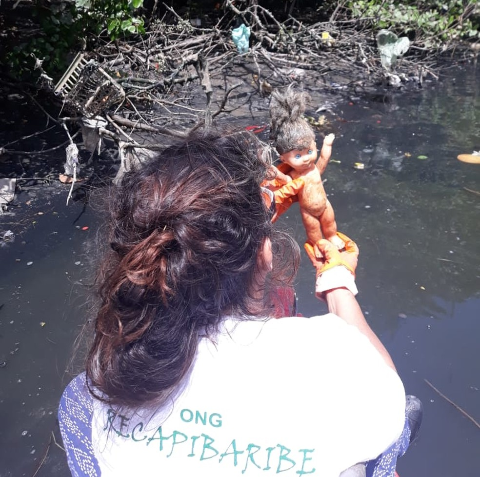 Voluntária encontra boneca em meio à sujeira na água do Rio Capibaribe — Foto: Socorro Cantanhede/Divulgação