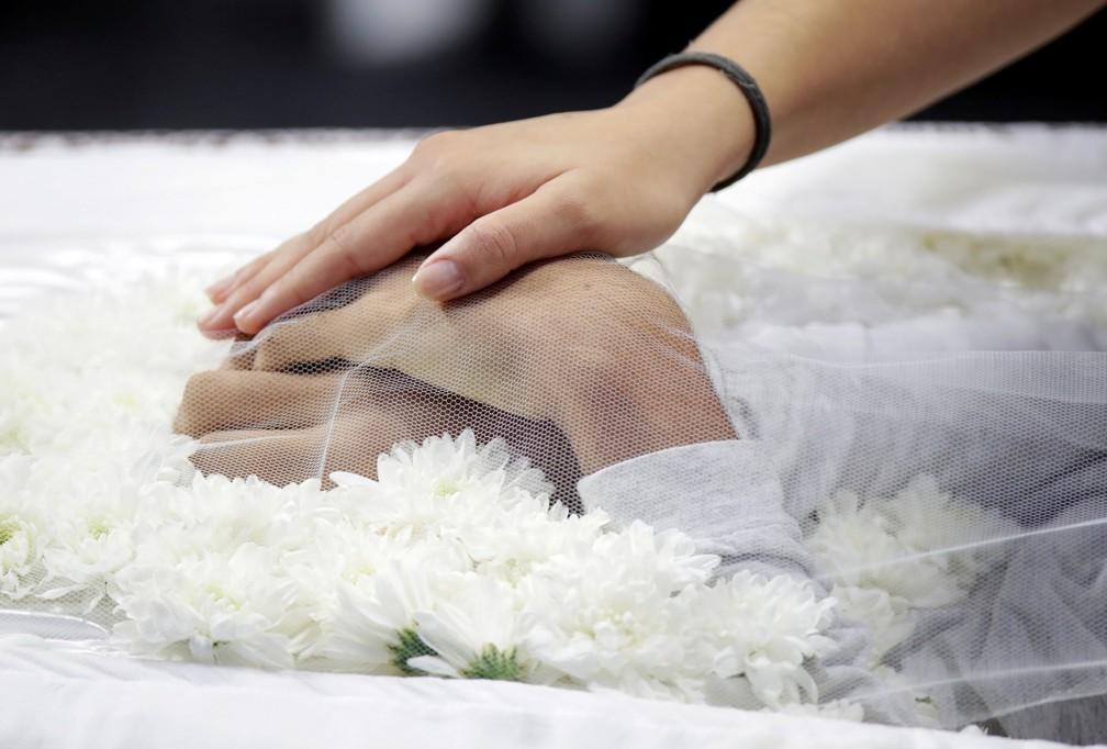 Uma pessoa toca as mãos de uma das vítimas do massacre na Escola Estadual Raul Brasil, em Suzano, durante velório coletivo nesta quinta-feira (14). Os corpos de seis vítimas foram velados no local — Foto: Ueslei Marcelino/Reuters