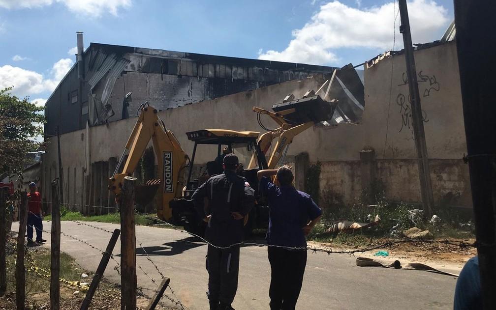 Bombeiros precisaram derrubar parte de muro da fábrica para que as equipes pudessem entrar em uma área do local em Salvador — Foto: Phael Fernandes/G1